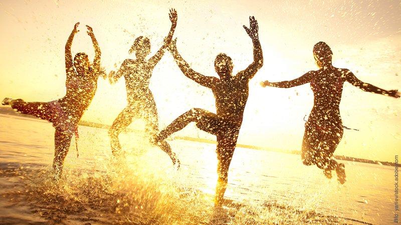 Untreue im Freundeskreis - 5 Blicke hinter die Kulissen. Mehrere Menschen im Gegenlicht plantschen und tanzen spritzend im flachen Wasser.