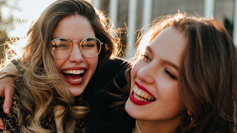 ER und SIE. Und ihre beste Freundin. Zwei Frauen lachen miteinander.