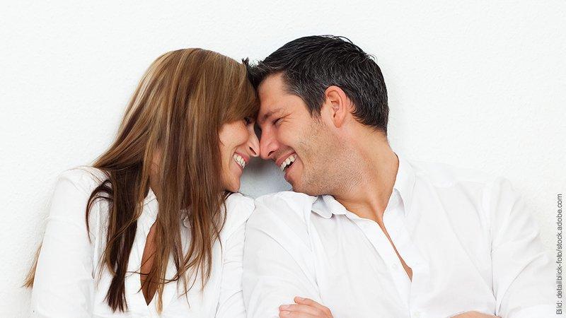 Zusammenziehen - 12 Fragen, die du vorher klären musst. Mann und Frau stecken zärtlich ihre Köpfe zusammen.