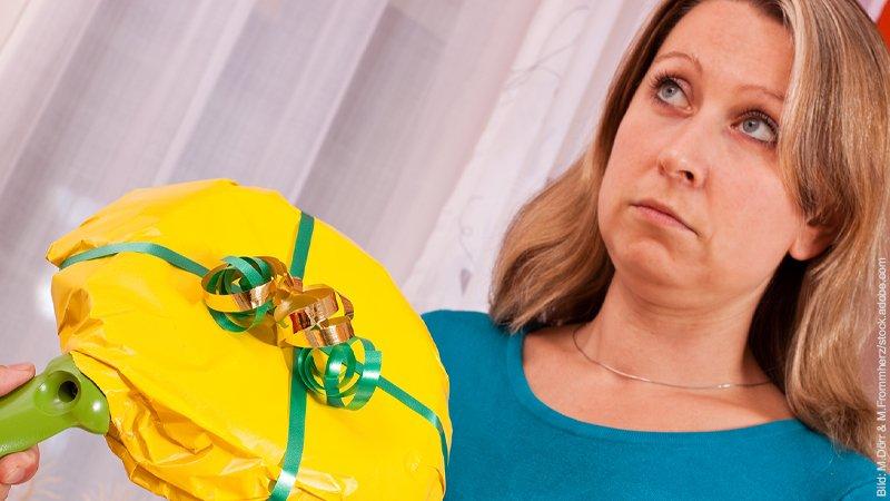 5 Regeln für ein entspanntes Weihnachten. Frau schaut sehr skeptisch, ihr wird ein Geschenk überreicht, das deutlich sichtbar eine Bratpfanne ist.
