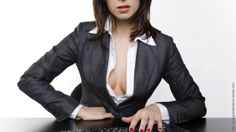 Fremdgehen mit Kollegen. Frau im Anzug sitzt mit halb offenen Bluse vor einer Tastatur.
