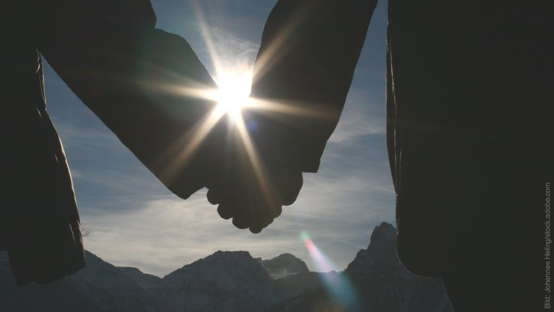 Unbekannte Fakten über Treue. Paar hält sich an den Händen. Gegenlicht.