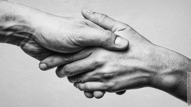 Das wichtigste Prinzip, um Fremdgehen zu vermeiden. Schwarz-weiß Foto. Hände, die wie in einem Händedruck abgebildet sind.