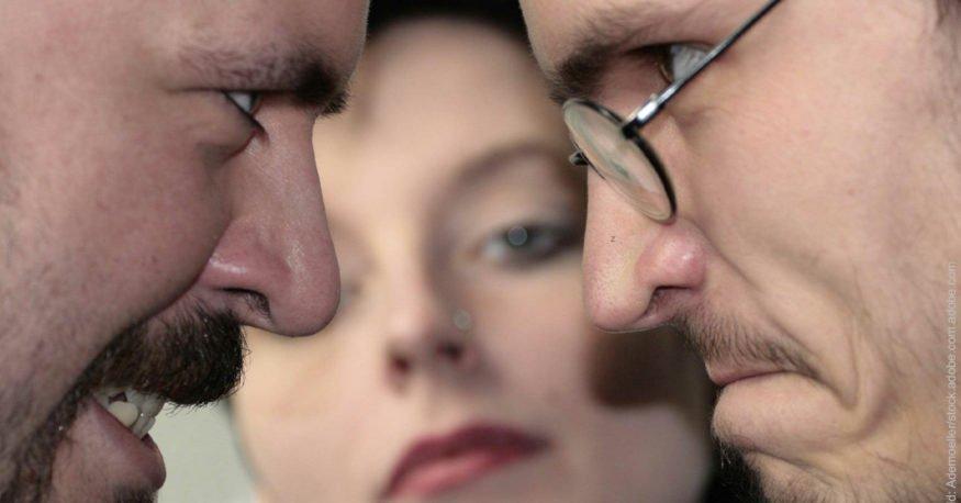 Gilt Eifersucht als Liebesbeweis? Zwei Männer schauen sich wütend an, Frau schaut unbeteiligt.