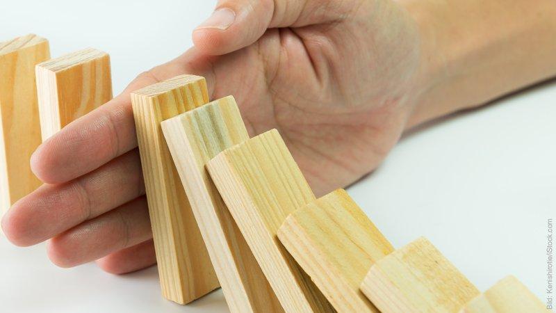 Beziehungskrise – Krisen bewältigen. Umfallende Domino-Steine, die von einer Hand in der Kettenreaktion gestoppt werden.