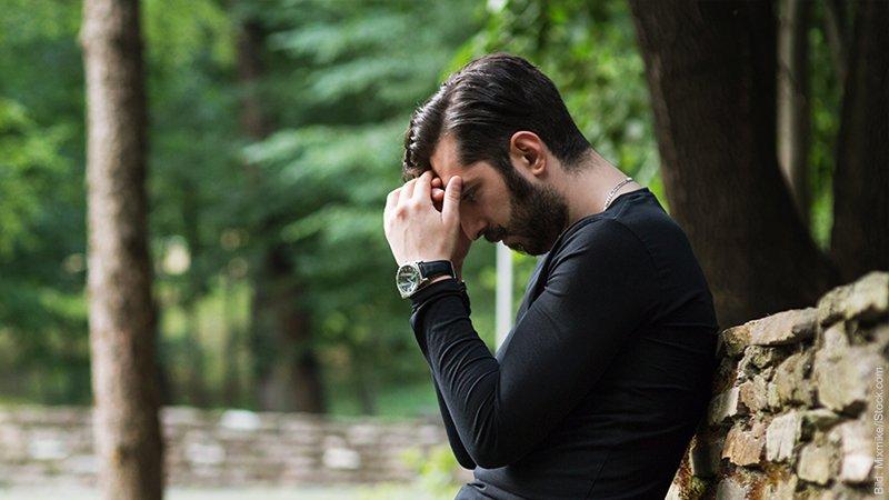 Die 7 Phasen der Trennung. Mann stützt den Kopf in die Hände, er sieht verzweifelt aus.