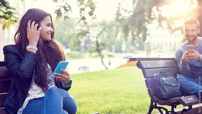 Die 7 Phasen der Trennung. junge Frau flirtet mit jungem Mann im Park.