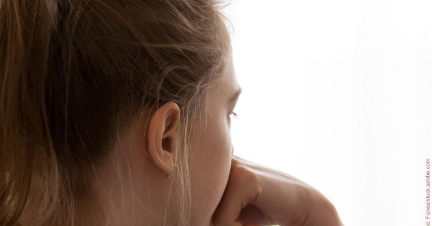 Einsamkeit nach der Trennung: Junge Frau von hinten, schaut in die Ferne.