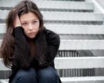 Phasen der Trennung: junge Frau sitzt auf einer Treppe und sieht traurig aus