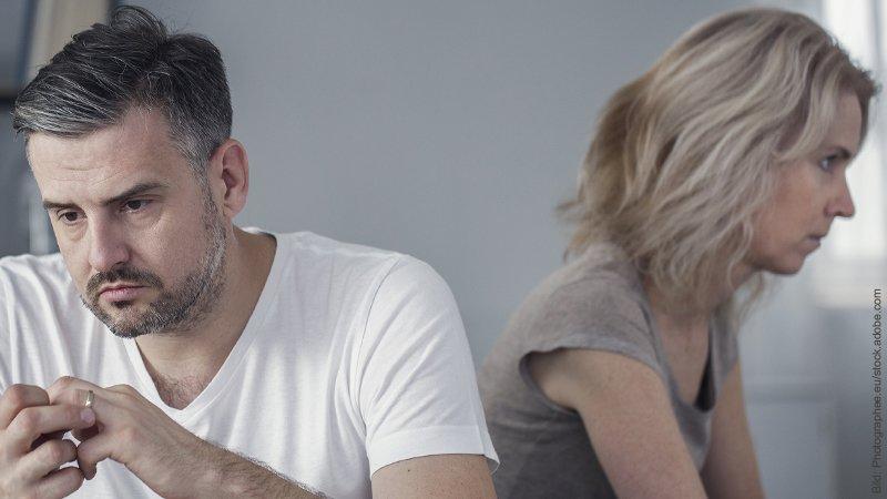 Trennen oder bleiben? Mann und Frau sitzen verzweifelt nebeneinander. Jeder schaut in eine andere Richtung.
