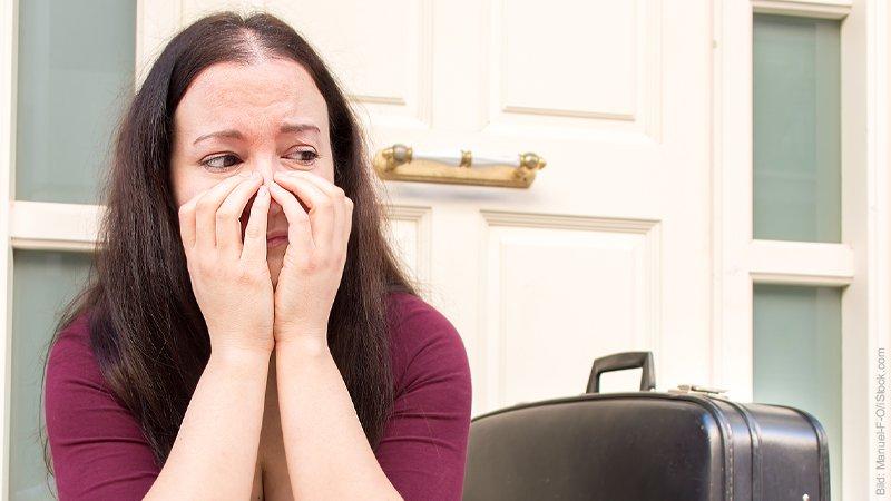 Trennung vorbereiten. Frau sitzt neben Koffer vor dem Haus. Sie hat die Hände vor dem Gesicht und sieht traurig aus.