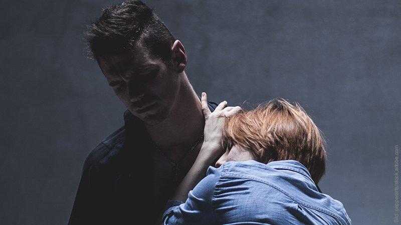Wie lange dauern Affären. Mann und Frau. Frau klammert sich an die Schultern des Mannes, der Mann schaut abweisend.