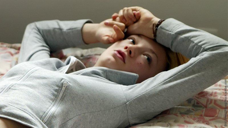Partner lässt schlechte Laune an mir aus: was tun? Junge Frau liegt auf dem Bett und schaut verzweifelt.