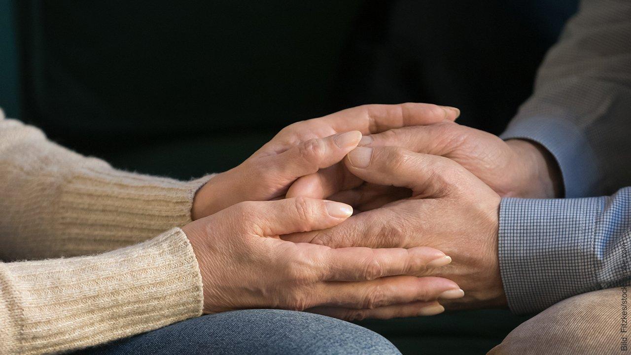 Streit beenden. Mann und Frau legen ihre Hände ineinander.
