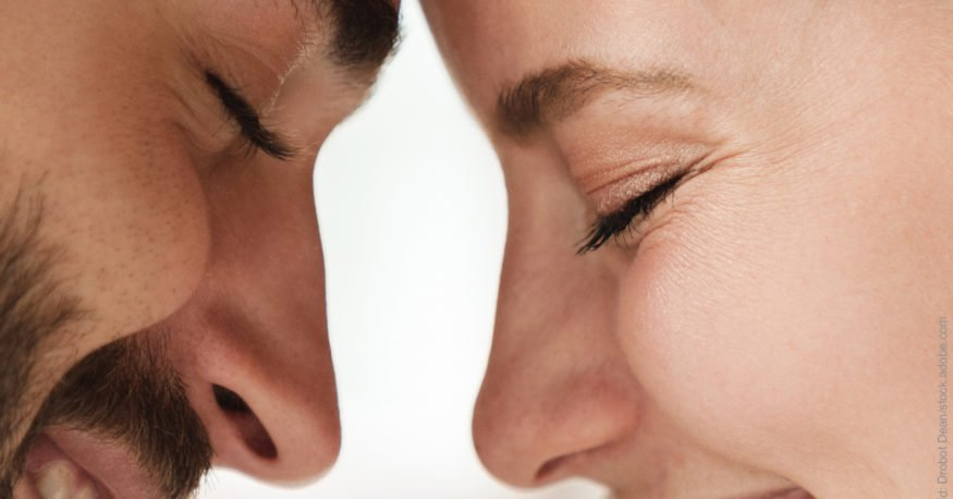 Streit Prophylaxe. Mann und Frau lächelnd mit geschlossenen Augen, Stirn an Stirn.