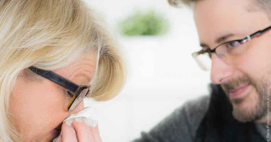 Versöhnung nach Streit. Mann tröstet Frau, die ihre Nase in ein Taschentuch hält.