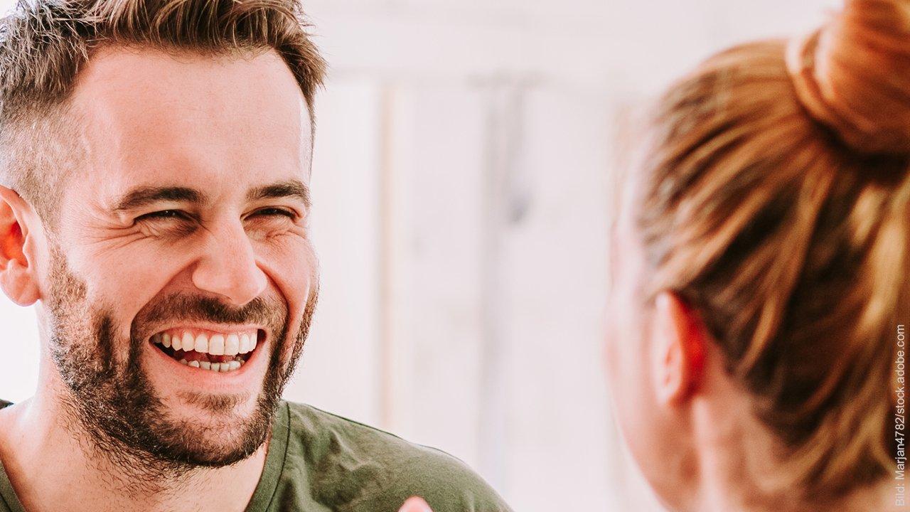 11 Gründe, warum wir andere unterbrechen. Mann lacht Frau an, Frau ist nur von hintern zu sehen.