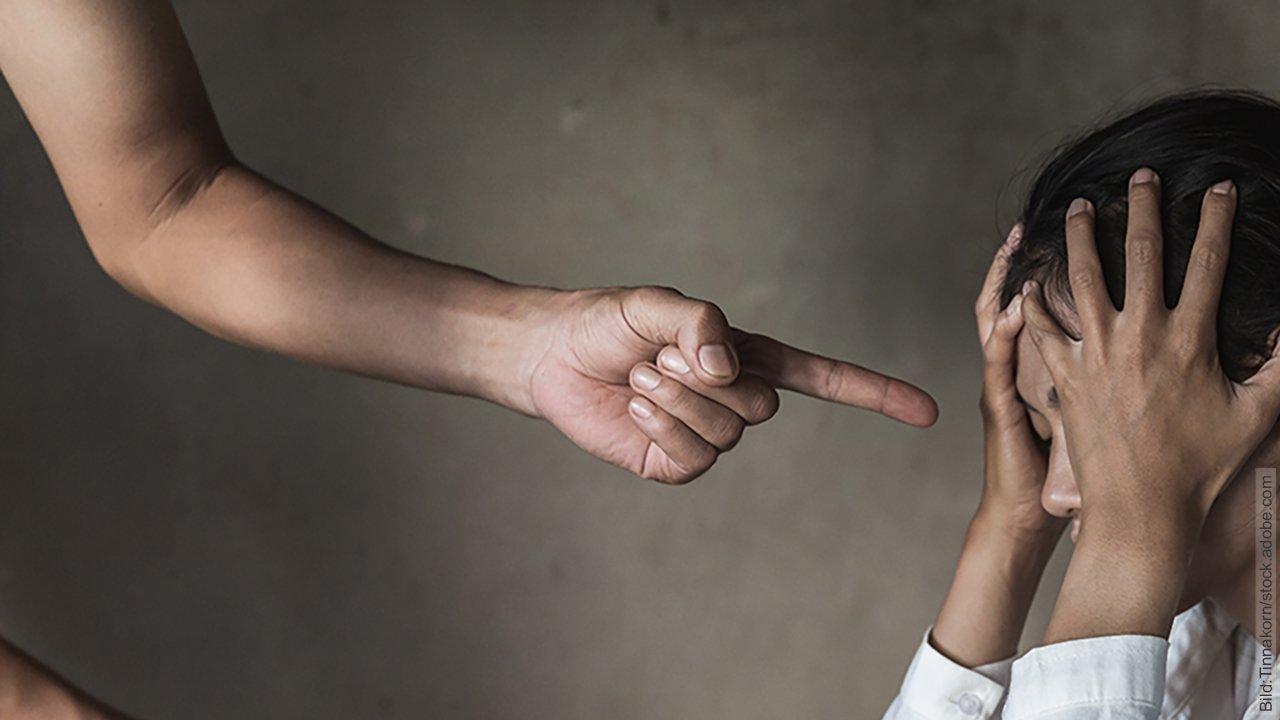 Gaslighting: Gehirnwäsche in der Partnerschaft. Mann zeigt mit dem Finger auf eine Frau, die die Hände vor ihr Gesicht hält. Vielleicht versucht er sie, durch Aggression zu manipulieren oder zu gaslighten,