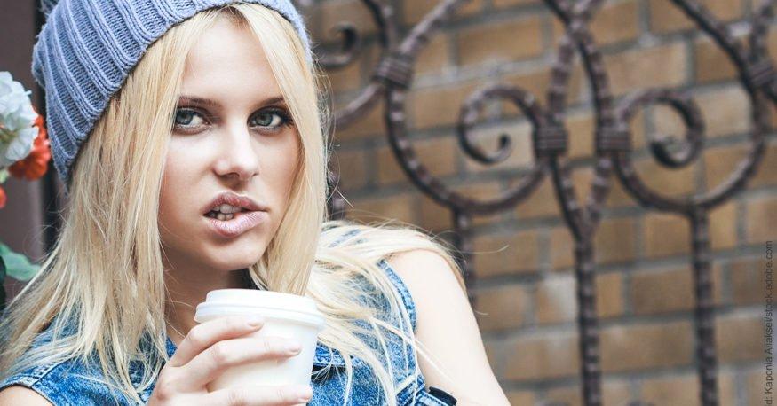Unterbrechen schwer gemacht – 7 Tipps. Junge blonde Frau mit Kaffee-Becher in der Hand beißt sich auf die Lippe. Sie überlegt offenbar, was sie tun will, wenn sie wieder unterbrochen wird.