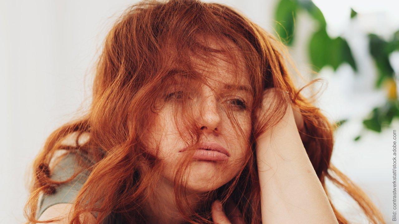 Wut und Hilflosigkeit nach dem Fremdgehen. Rothaarige Frau stützt den Kopf auf, sieht wütend aus, hat zerwühlte Haare und schaut hilflos.