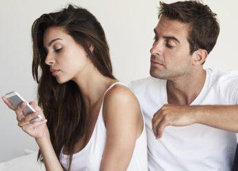 Eifersucht und Trennung. Mann schaut eifersüchtig zu seiner Frau, die in ihr Handy schaut. Beide sitzen auf dem Bett. Ob eine Trennung bevorsteht?