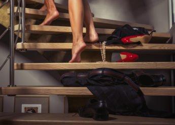 Flirten, Fremdgehen und Affären. Kleidung liegt überall, Mann und Frau gehen nackt eine Treppe hoch.