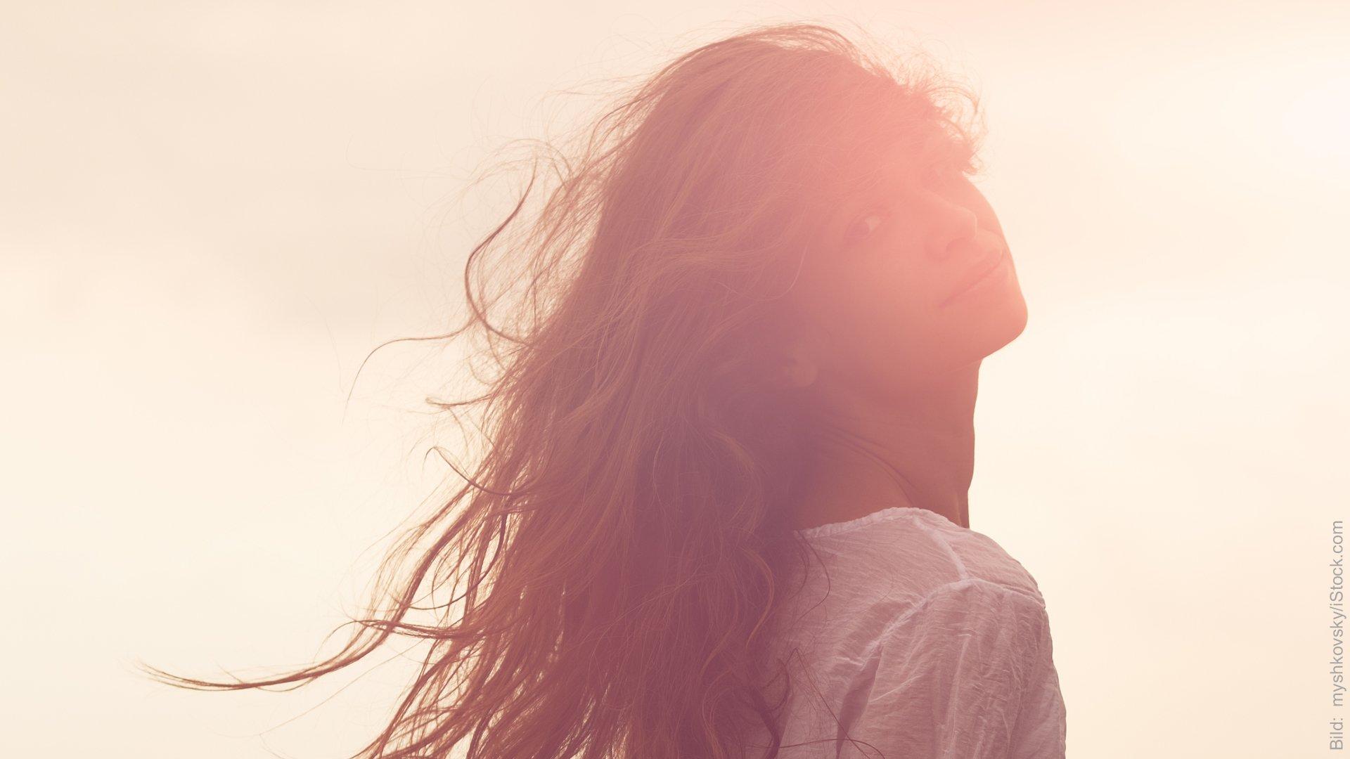 Neurowissenschaft in der Paartherapie. Frau im Gegenlicht. Sie blickt über ihre Schulter, ihre langen Haare wehen im Wind.