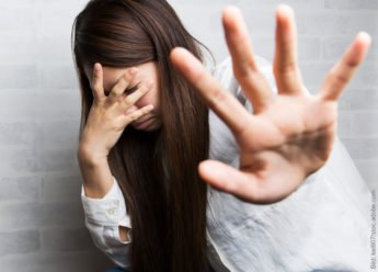 Stress, Angst und Panik. Frau hält Hand abwehrend hoch. Sie sieht ängstlich aus, gestresst und könnte auch gerade Panik vor etwas haben.