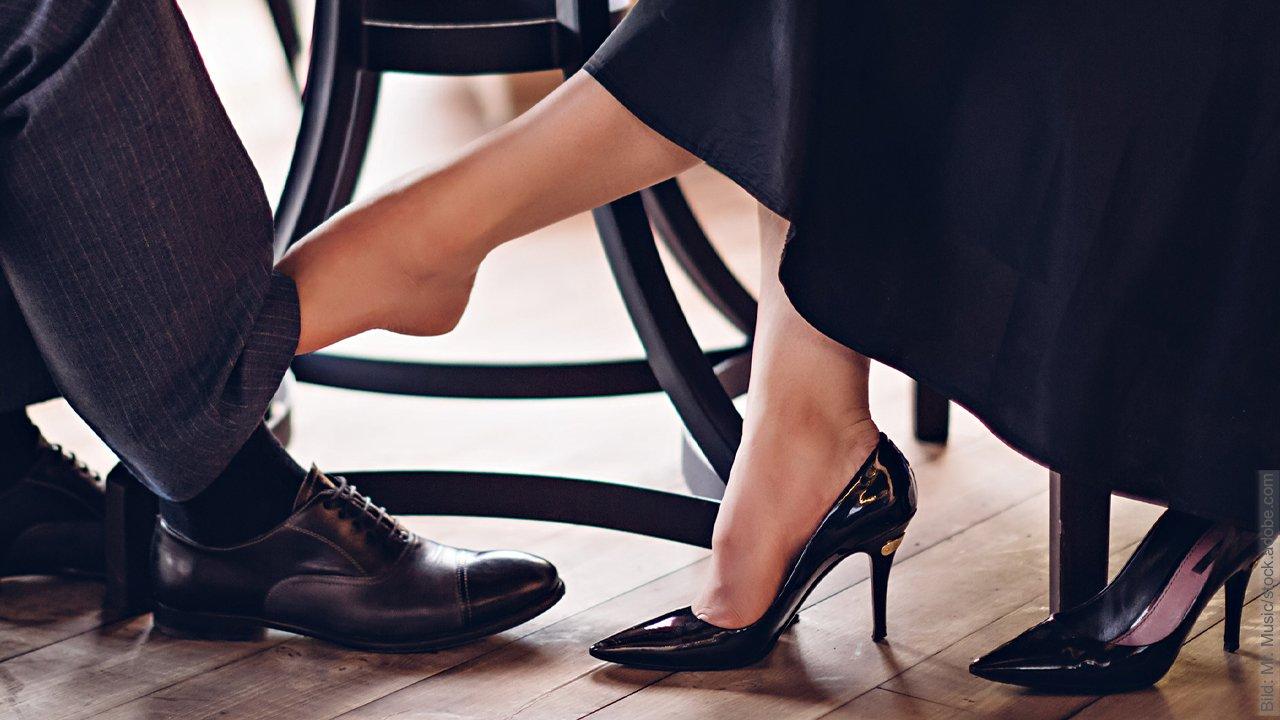 Sexualisierung in der Partnerschaft mal anders herum: Frau hat Schuh ausgezogen und berührt damit einen Mann am Bein unter einem Tisch.